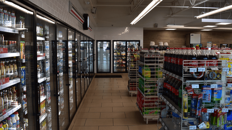 Indoor image of 7-11 showing the deli display fridge and soda machines.