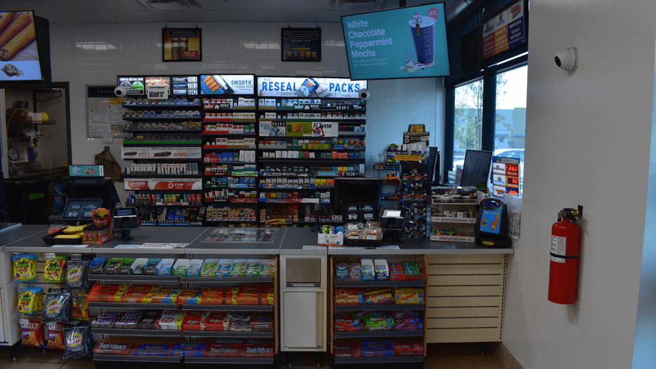 Indoor image of 7-11 showing the hot foods display and condiment area.
