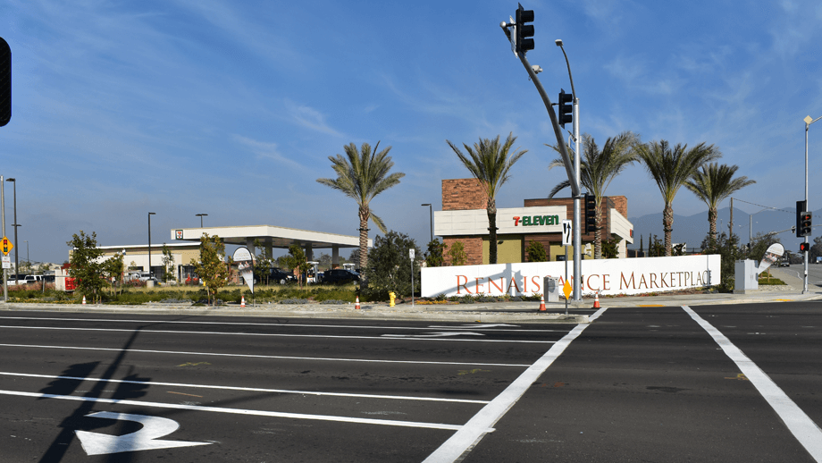 Outdoor image of 7-11 intersection showing palmtrees, streetlights, and a sign that reads 'Renaissance Marketplace'.