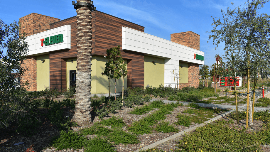 Outdoor image of 7-11 building back entrance with greenery in the foreground.