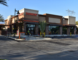 Outdoor image of Dunkin Donuts showing the builidng facade and parking lot.