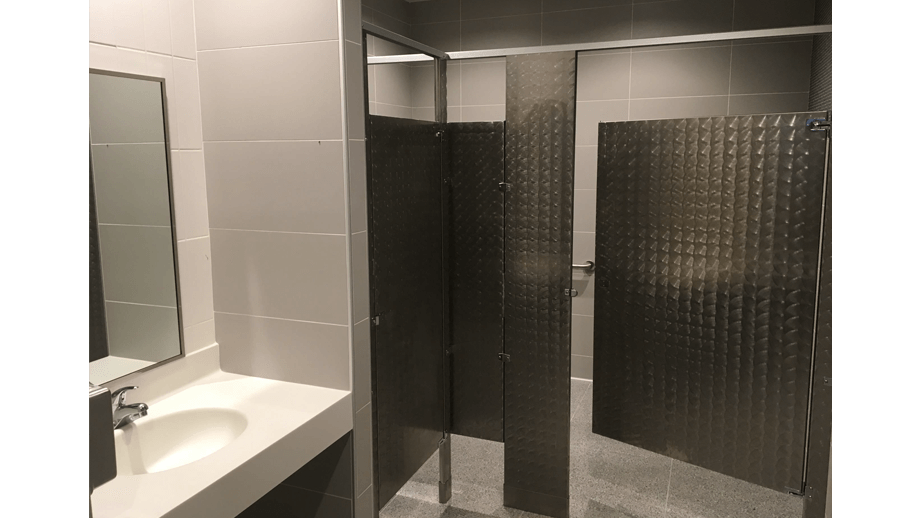 Indoor image of McDonalds showing bathroom stall and mirror.