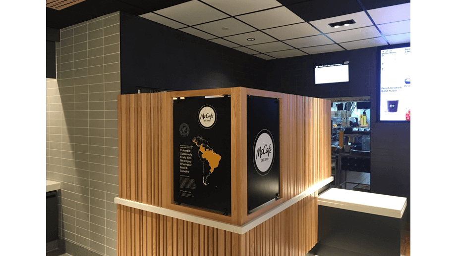 Indoor image of McDonalds showing wooden backboard and two black McCafe signs.