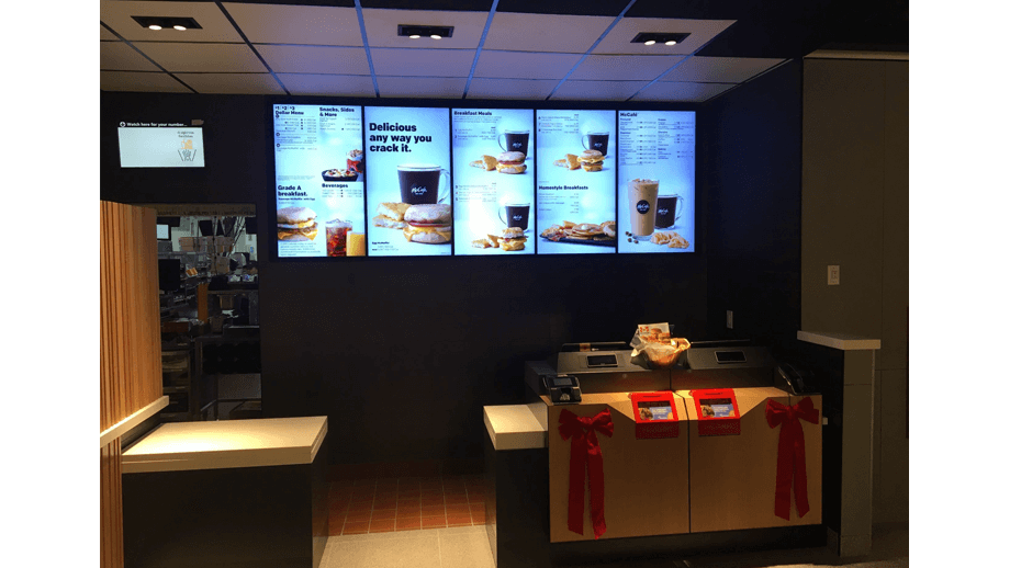 Indoor image of McDonalds showing cashier area and menu screens.