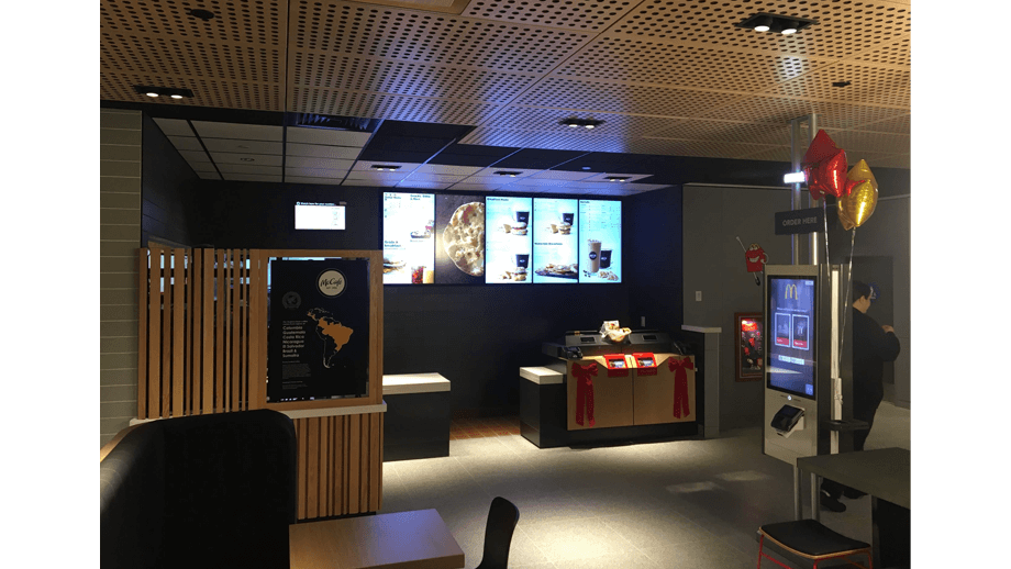 Indoor image of McDonalds showing cashier area, order kiosk, and menu screens.