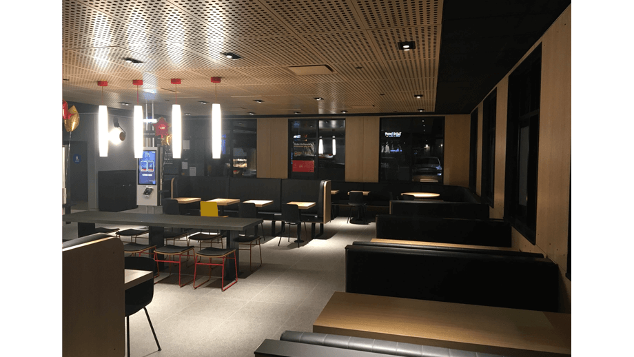 Indoor image of McDonalds showing dining area booths, chairs, tables, and stools.