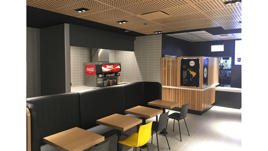 Indoor image of McDonalds showing dining area booths, chairs, and soda machine.