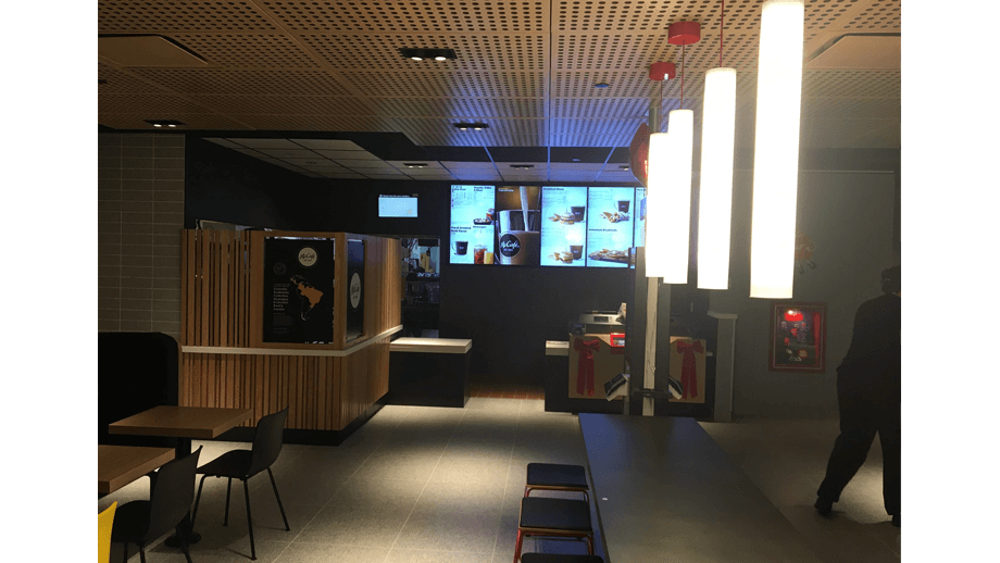 Indoor image of McDonalds showing dining area main table, stools, and menu screens.