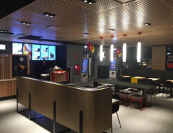 Indoor image of McDonalds showing fabric booths and tall ceiling lamps.